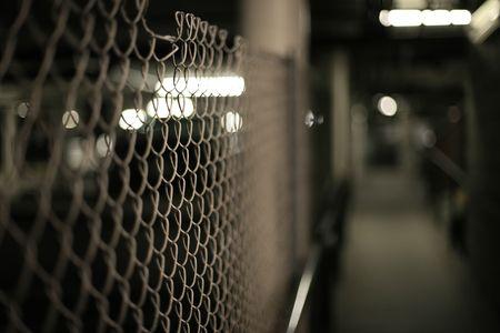 Mesh fence in an underground garage structure. Shallow DOF. photo