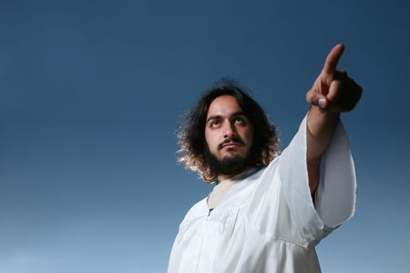 worship white: Man looking like Jesus pointing his finger, dramatic blue sky behind. Stock Photo