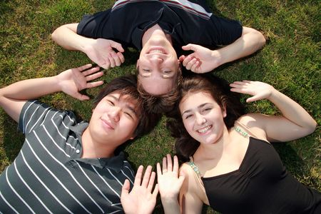 liesure: Three happy friends lying on green grass smiling with heads together.