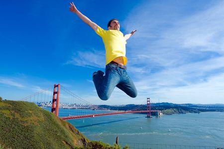 Happy jongeman springen hoog in de lucht naast de Golden Gate brug, San Francisco, Californië