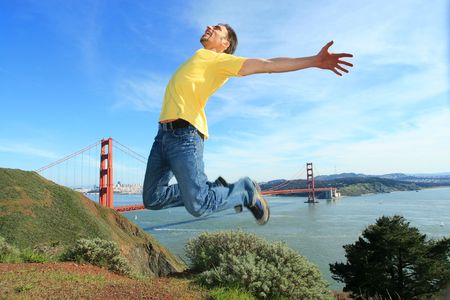 triumphant: Happy young man jumping high in the air next to the Golden Gate bridge, San Francisco, California