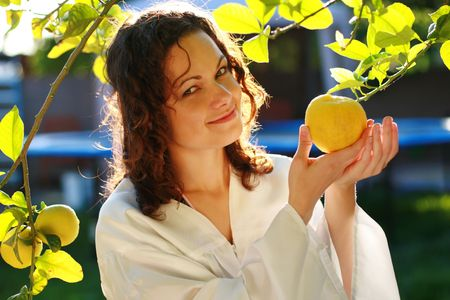 Young woman picking up a fresh lemon from tree photo