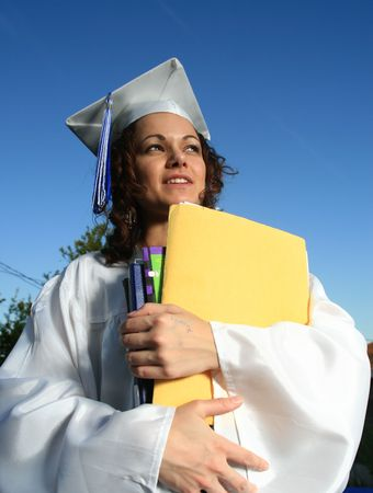 Happy graduate female student holding a big pile of textbooks and folders photo