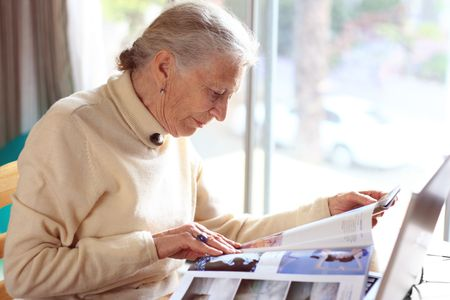 Elderly lady reading magazine. Shallow DOF. Stock Photo - 2483281