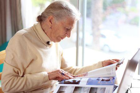 shallow dof: Elderly lady reading magazine. Shallow DOF.