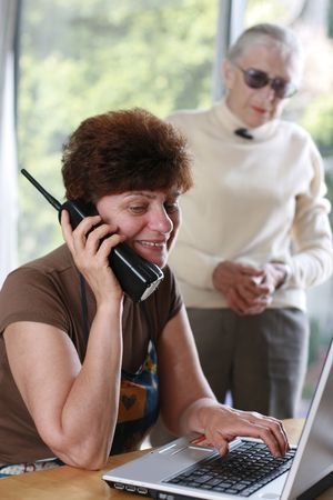 Mature woman talking on the phone, her mother listening behind. Stock Photo - 2483279