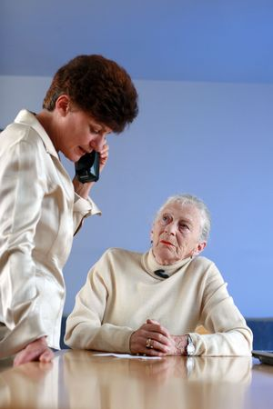 Elderly woman on appointment with social worker. Shallow DOF, focus on elderly lady. photo