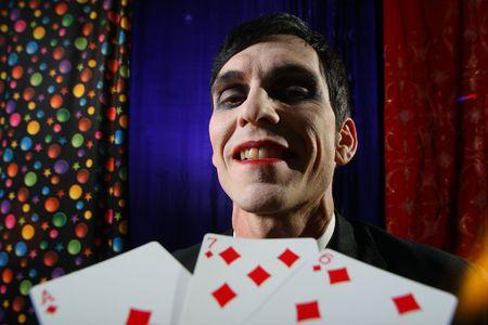seven persons: Smiling Joker face. Dramatic light.