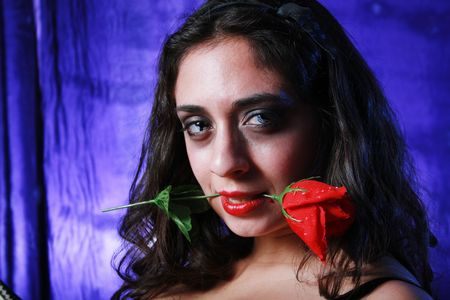 Young beautiful brunette with red rose in her mouth photo
