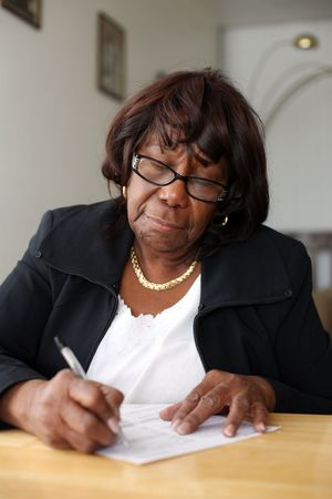 writing on glass: Elderly African American woman writing a letter. Shallow DOF. Stock Photo