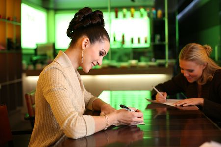 Beautiful young businesswoman writing photo