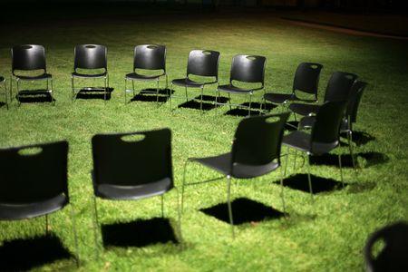 Circle of black chears on green grass at night. Shallow DOF. photo
