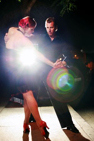 Beautiful couple dancing tango on night street, dramatic light. Stock Photo