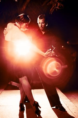 Beautiful couple dancing tango on night street, dramatic light. Banco de Imagens