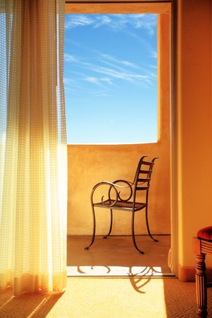 accomodation: Elegant metal chair on sunny balcony, blue sky behind.