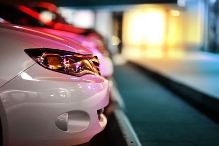 Modern car detail on night parking lot. Shallow DOF. Stock Photo