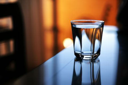 reflects: Glass of water reflects in glass table