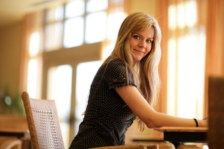 Portrait of a beautiful young blond woman relaxing in sunny interior. Shallow DOF. photo