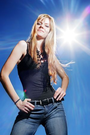 jeans girl: Beautiful girl over blue sky with hot sun.