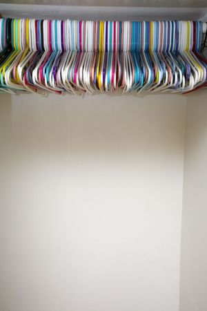 Colorful hangers in empty white closet photo