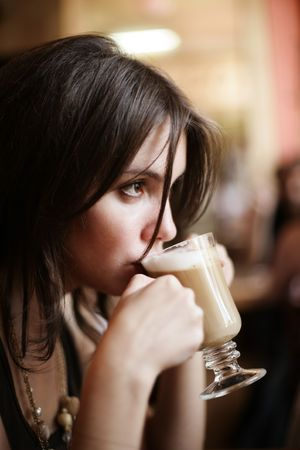 sipping: Beautiful young girl sipping coffee lattee. Shallow DOF.
