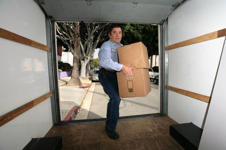 moving truck: Man in blue shirt carrying cardboard boxes into empty truck.