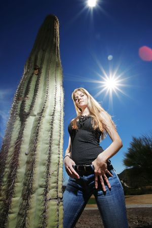 Hot girl in Arizona standing next to a huge Saguaro Cactus. Wide angle view.
