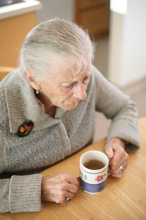 Senior woman with cup of tea at home. Shallow DOF. Stock Photo