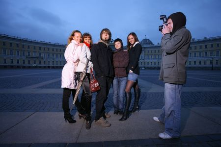 Photographer taking a fashion photo of a small group of young people. photo