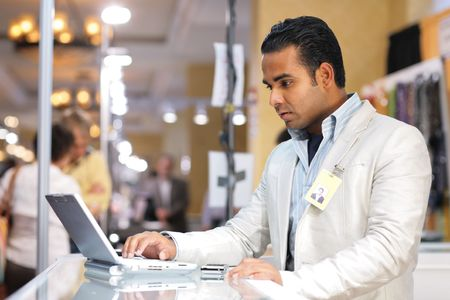 Young indian businessman using laptop computer at trade show. photo