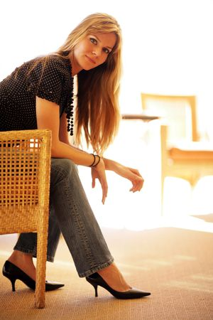 Beautiful young woman sitting in chair photo