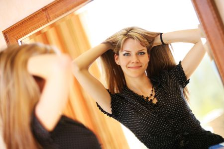 Beautiful young woman looking in the mirror Stock Photo