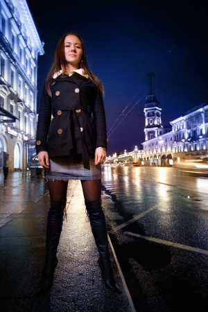 Beautiful young woman standing on illuminated street at night. 版權商用圖片