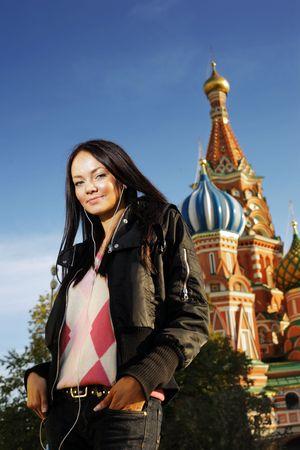 red square moscow: Mujer joven hermosa al lado de la catedral de la albahaca de Santo en el cuadrado rojo, Mosc�, Rusia.