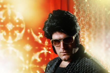 elvis: Elvis Presley impersonator over glowing background.