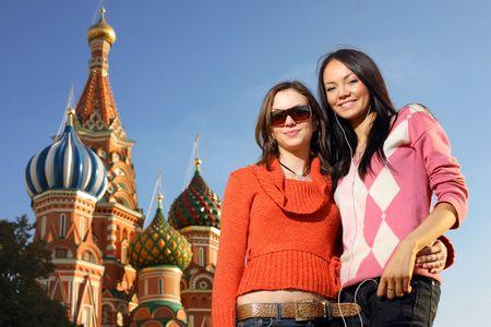 red square moscow: Dos mujeres j�venes hermosas al lado de la catedral de la albahaca de Santo en el cuadrado rojo, Mosc�, Rusia.
