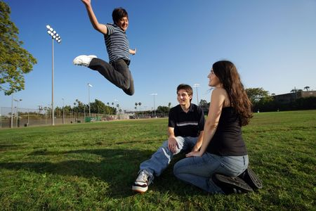 Three young friends outdoors, one of them jumping. photo