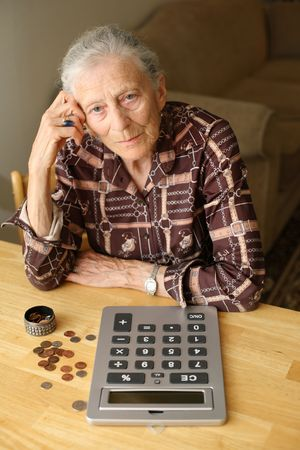 Senior woman counting money with calculator Stock Photo