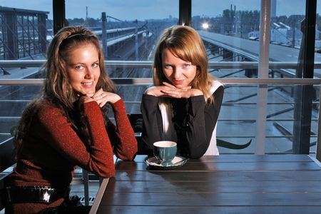Two beutiful young women in restaurant with cup of tea photo
