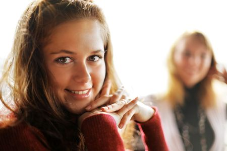 Two beautiful young women in restaurant with cup of tea photo