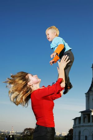 Young mother lifting small son in the sky. Stock Photo - 2750466