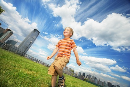 Boy running on green grass field under beautiful blue sky with scenic white  clouds. photo