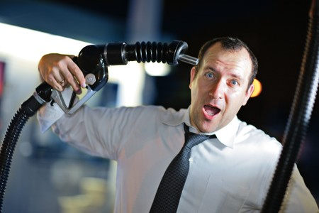 Businessman putting gas nozzle to his head, screaming. photo