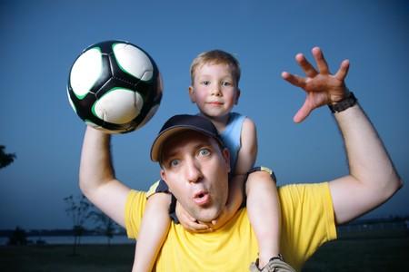 jugando al futbol: Padre e hijo jugando al f�tbol al aire libre