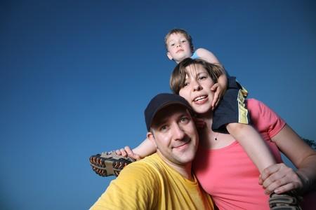 Happy family outdoors over blue sky photo