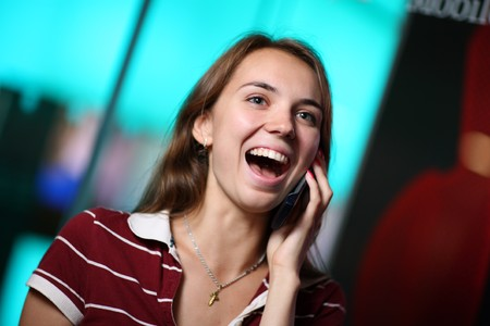 Happy young woman talking on cellular phone photo