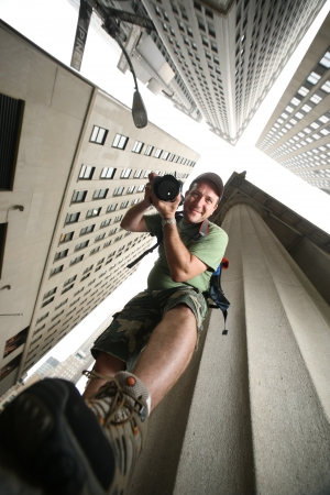 Photographer in New York City. Wide angle view from below.
