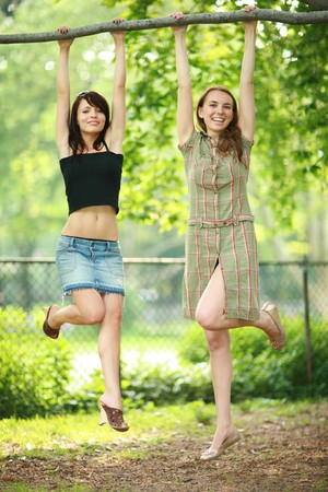 mini skirt: Two beautiful girls hanging on tree branch in park, laughing. Shallow DOF.