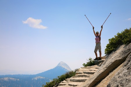 spreaded: Happy young woman standing  on top of a mountain with arms rised Stock Photo