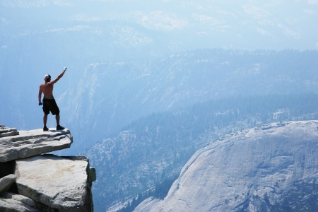Man standing on top of a cliff with arm raised Stock Photo
